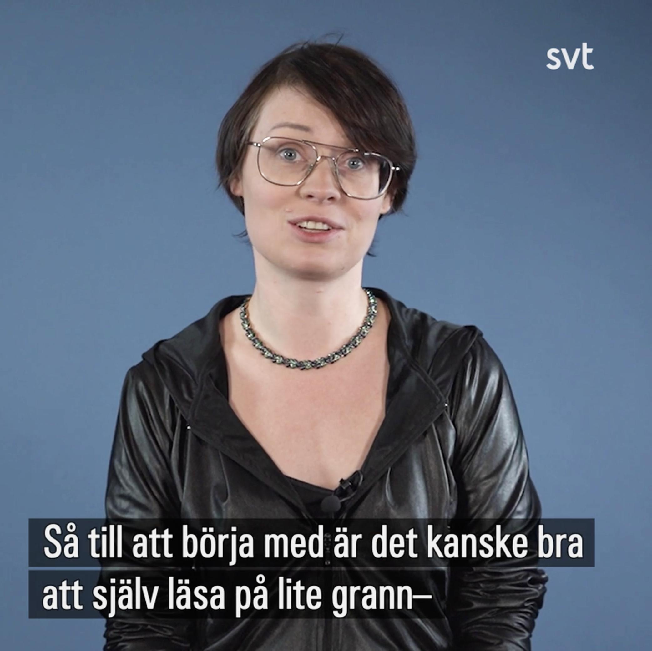 Tanja Suhinina sitter framför en blå bakgrund.