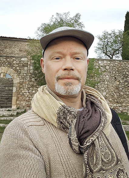 Person med stickad beige tröja står framför borg eller ruin