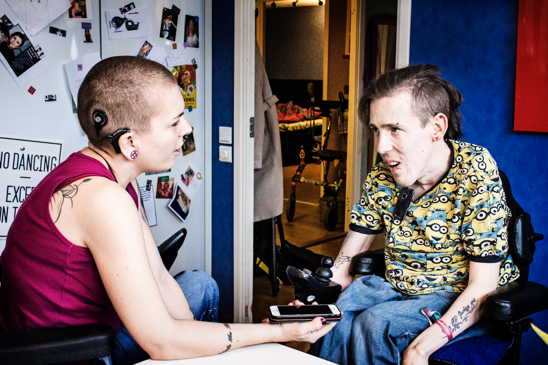Anders Eriksson intervjuas av Frida Ingha i hennes kök, båda sitter i sina rullstolar.