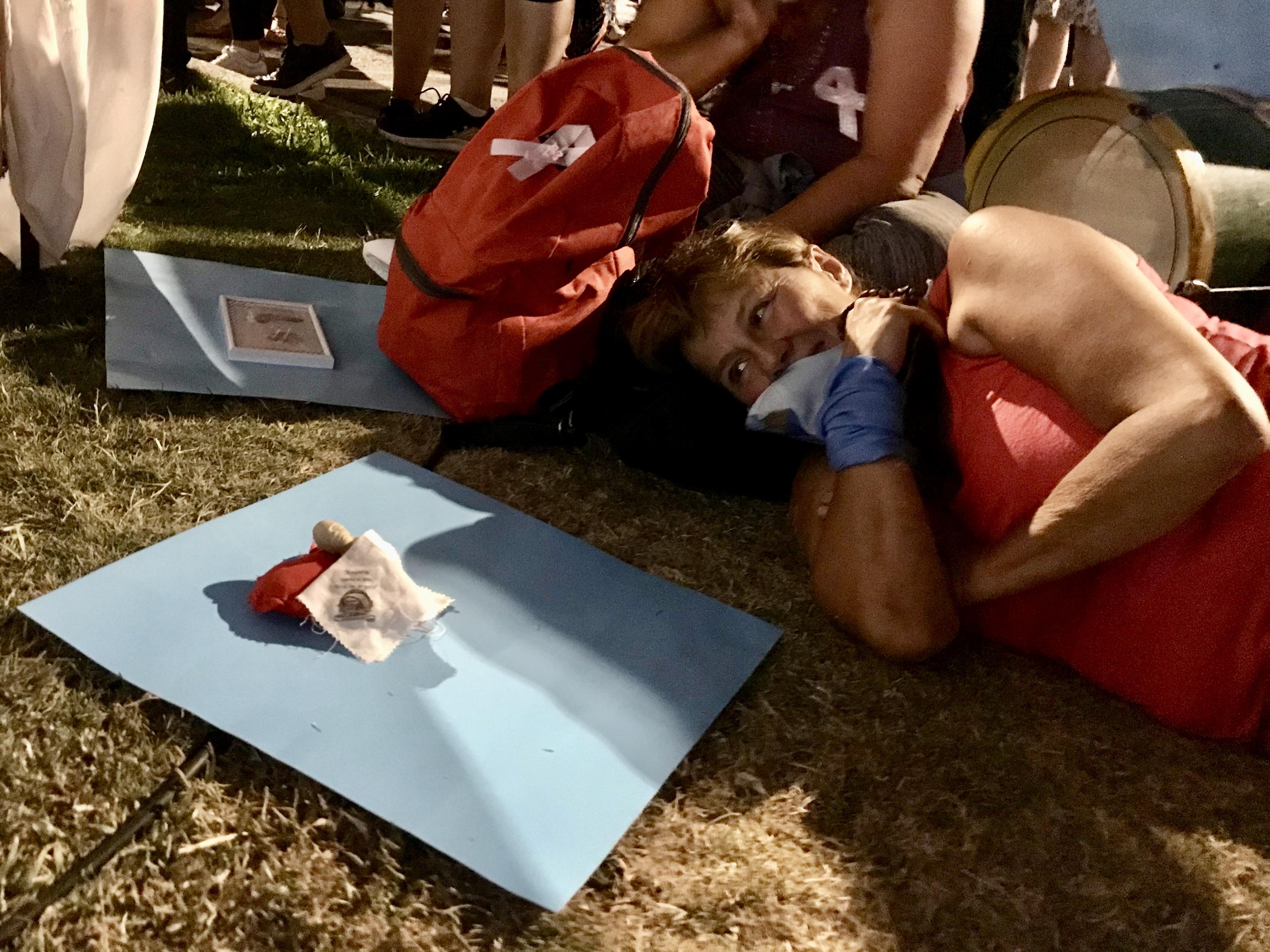 Abortmotståndaren Dolores Silveya liggandes i gräset bredvid ett blått plakat.