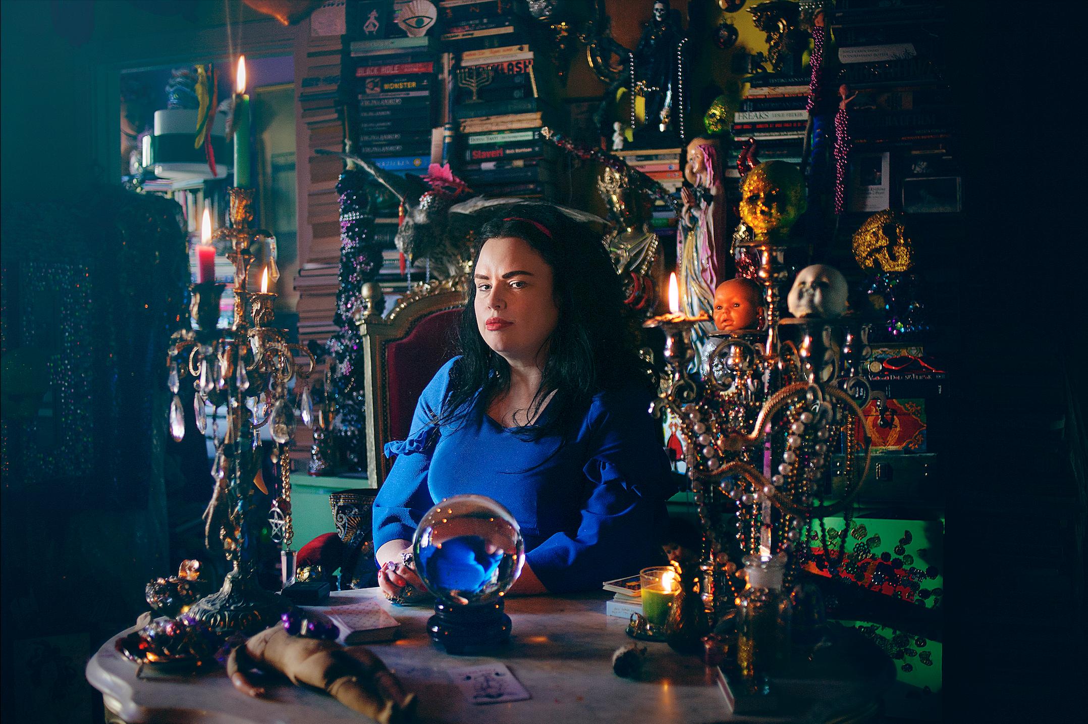 Linda Spåman sitter bakom ett bord med böcker, smycken och prydnader bakom.