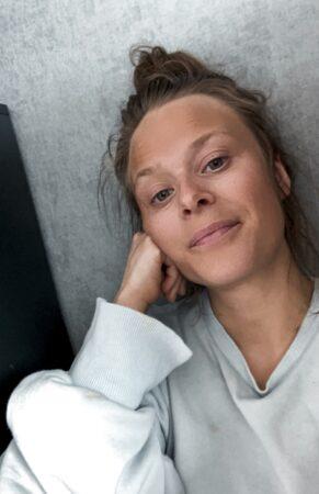 Lina Maria Viitala sitter mot en vägg och tittar in i kameran.